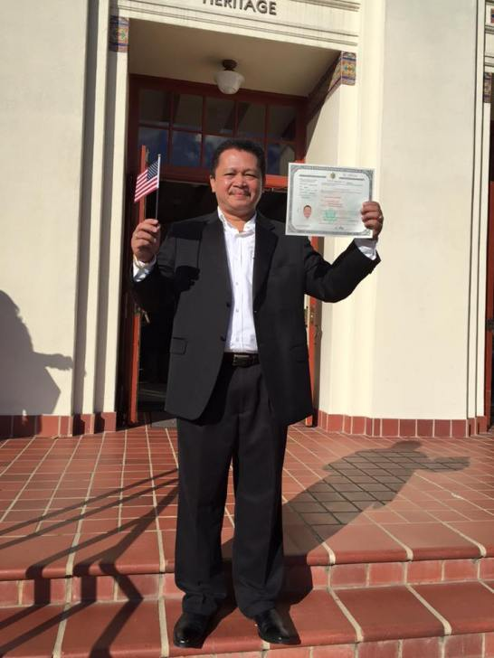 [My friend Ronie is shown in this photo proudly flaunting his US citizenship naturalization certificate with his left hand while toting a tiny US flag with his right hand]