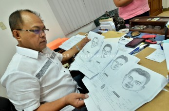"""DAVAO. National Bureau of Investigation Regional Director Dante Gierran looks at the artist sketch of suspects in the ambush-slay last month of Mayor Reynaldo Navarro of Laak, Compostela Valley that has become embroiled in the case against Sr. Supt. Leonardo Felonia. (King Rodriguez)"""