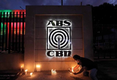 An employee lights candles in front of the headquarters of broadcast network ABS-CBN on Tuesday, May 5, 2020, in Manila, Philippines. A government agency has ordered the country's leading broadcast network, which the president has targeted for its critical news coverage, to halt operations. (AP Photo/Aaron Favila)