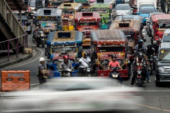 Jeepneys are seen as an enforcer manages traffic at a busy street in Manila on May 30, 2017.Jeepneys, once hailed as the 'King of the Road' and a cultural symbol in the Phillipines to rival New York's yellow taxis, may soon disappear from Manila's gridlocked streets, as authorities move to phase out the Philippines' iconic World War II-era minibuses, citing pollution and safety concerns. / AFP PHOTO / NOEL CELIS / TO GO WITH AFP STORY PHILIPPINES-JEEPNEY-CULTURE-TRANSPORT,SCENE