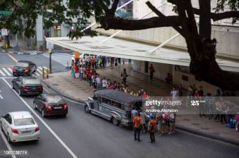 People queueing up to board the local free Jeepney in Makati, Metro Manila, Philippines. A Jeepneys, or Dyipni in Filipino, are repurposed US military jeeps left over from WWII that have become a prevalent symbol of Philippine art and culture. (photo by Andrew Aitchison / In pictures via Getty Images)